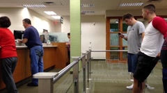 One side of people waiting and checking message inside TD bank Stock Footage