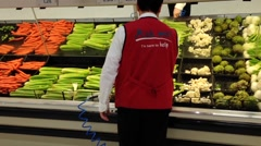 Worker pouring water on vegetables for sale in grocery store Stock Footage