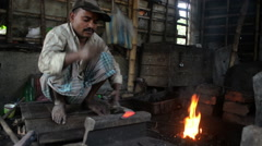 Wide shot of an Indian blacksmith making a sickle. Stock Footage