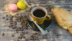 Coffee and croissant and macarones rotating on wooden table. - stock footage