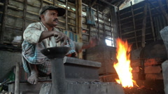 A candid wide shot of an Indian blacksmith doing his daily job. Stock Footage