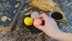 Girl's hand puts a cup of coffee and taking macaroon Stock Footage