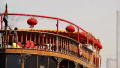 Red chinese paper lantern hang around open top deck of wood dhow boat Stock Footage