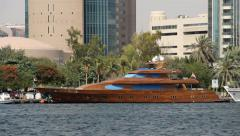 Modern luxury yacht with wood hull parked at Dubai Creek Stock Footage