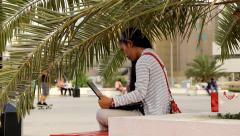 Asian woman sit with laptop on bench under palm frond, boys on skates Stock Footage
