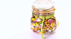 Colorful candies in glass candy jar on a white background. Stock Footage