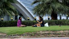 Two young Indian women sit at lawn against Union metro station, talk Stock Footage