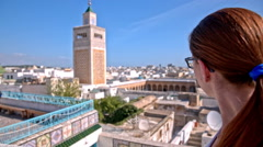Woman observing minaret in city of Tunis Stock Footage