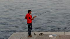 Stock Video Footage of Pakistani men make unsuccessful throw by fishing rod, fail to cast the line