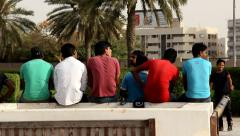 Group of men sit back to camera, different colors of t-shirt and polo Stock Footage