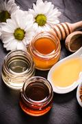 Honey in jar with honey dipper on black stone background - stock photo