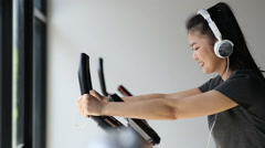 Asian women use bicycle in gym and listening music Stock Footage