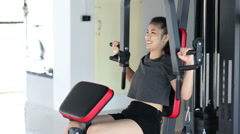 Young asian woman use shoulder press machine Stock Footage