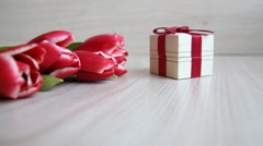 Hand shifts gift box with a red bow next to the tulips Stock Footage