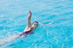 Woman in goggles swimming front crawl style Stock Photos