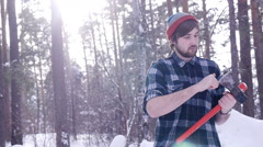 Lumberjack stands and sharpens his ax in the woods, light leakage surround him - stock footage