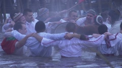Bulgarian old tradition men bathe in the icy waters of the river - stock footage