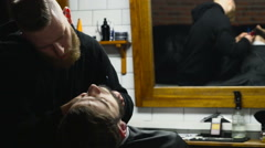Barber shaves the beard of the client with trimmer slow motion - stock footage