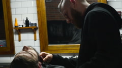 Barber shaves the beard of the client with trimmer slow motion Stock Footage