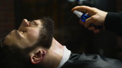 barber applying the lotion after shaving on customers neck and face slow motion - stock footage