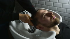 Barber washes customer hair slow motion Stock Footage