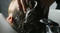 Barber washes customer hair slow motion close up Stock Footage