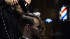 Barber drys customers hair before haircut slow motion Stock Footage
