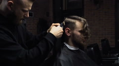Barber cuts the hair of the client with clipper slow motion - stock footage
