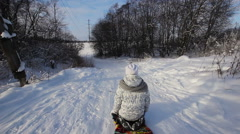 Yong girl sledging down hill Stock Footage