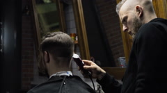 Barber cuts the hair of the client with trimmer slow motion - stock footage