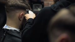 Barber cuts the hair of the client with clipper slow motion Stock Footage