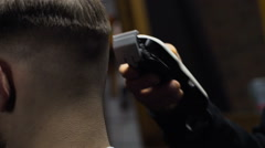 Barber cuts the hair of the client with clipper slow motion close up Stock Footage