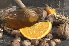 Stock Photo of Honey, nuts, wheat and orange fruit on an old vintage planked wood table.