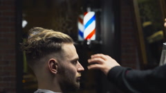 Barber spraying customers hair before the haircut slow motion Stock Footage