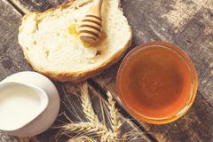 Stock Photo of Honey in a jar, bread, wheat and milk on wood table.