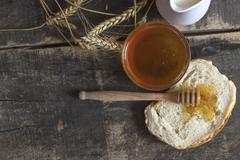 Honey in a jar, bread, wheat and milk on wood table. - stock photo