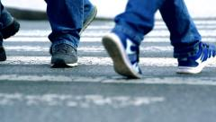 Slowmotion detail view of shoes from people who pass the crosswalk Stock Footage