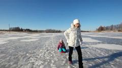 Girl sledding sister on frozen lake Stock Footage