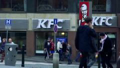 Slowmotion people walk on sidewalk in front of KFC shop. Stock Footage