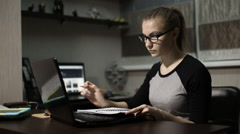 Young student in front of a laptop to take notes in a notebook at night Stock Footage