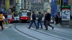 Slowmotion pedestrians go across rail near by tram. Stock Footage