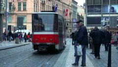 Slowmotion people stand on stop and tram goes away. Stock Footage