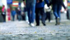 Slowmotion detail of sidewalk and people who walk on background Stock Footage
