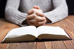 Woman hands praying with a bible in dark over wooden table Kuvituskuvat