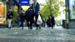 Slowmotion blurry view on people who walk on sidewalk in town Stock Footage