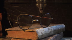 A pair of old glasses lying on top of torn old books. Stillife. Stock Footage