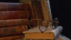 Old, aged, ancient and weathered books in a stack. A pair of old glasses. Stock Footage