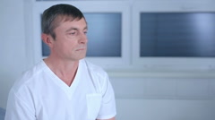 Distressed male patient holding head - stock footage