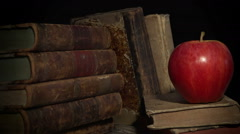 Stock Video Footage of Apple of knowledge and wisdom. Red apple and a pile of books.