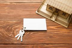 Real Estate Concept. Model house, keys, blank business card on wooden table. Top - stock photo